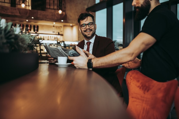 Jeune homme d'affaires payant avec une carte de crédit sans contact avec la technologie nfc.