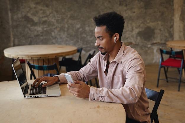 Jeune homme d'affaires à la peau assez sombre avec barbe travaillant hors du bureau, assis à table avec ordinateur portable et va passer un appel avec son smartphone, vêtu d'une chemise beige