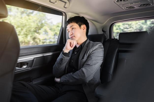 Jeune homme d'affaires pensant alors qu'il était assis sur le siège arrière de la voiture