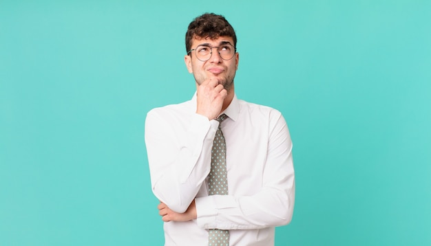 Jeune homme d'affaires pensant, se sentant dubitatif et confus, avec différentes options, se demandant quelle décision prendre