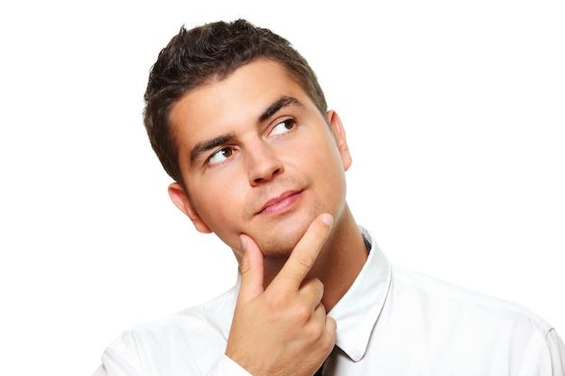 Un jeune homme d'affaires perdu dans ses pensées sur fond blanc
