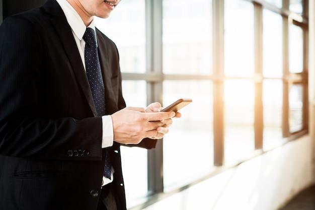 Jeune homme d'affaires permanent avec smartphone près de la fenêtre du bureau, concept d'entreprise