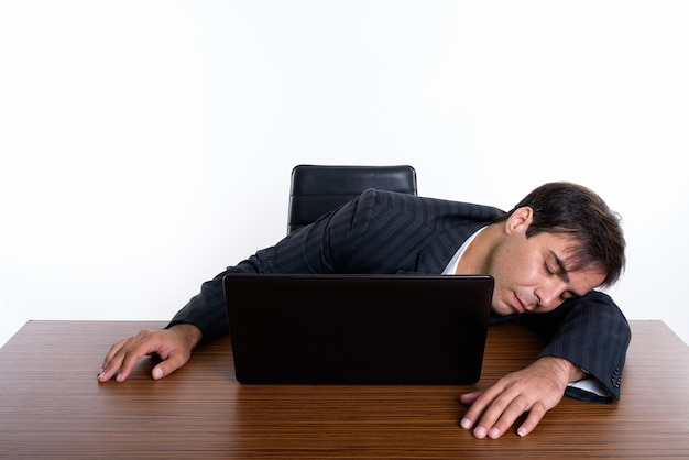 Jeune homme d'affaires persan dormir avec un ordinateur portable sur
