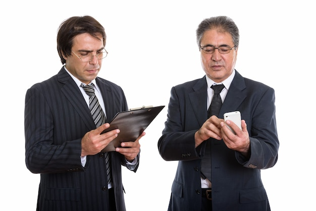 Jeune homme d'affaires persan lisant sur le presse-papiers et un collègue senior regardant smartphone