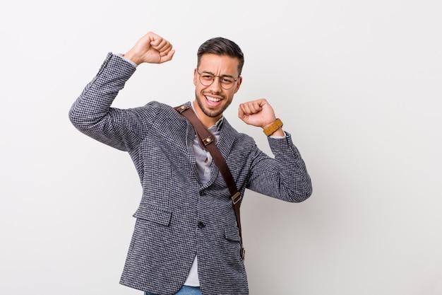 Jeune homme d'affaires philippin célébrant une journée spéciale, saute et lève les bras avec énergie