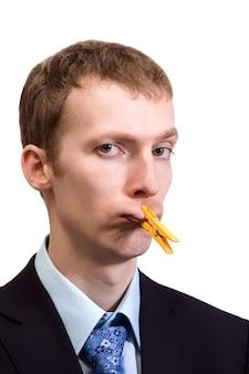 Jeune homme d'affaires avec une pince à linge jaune sur la bouche