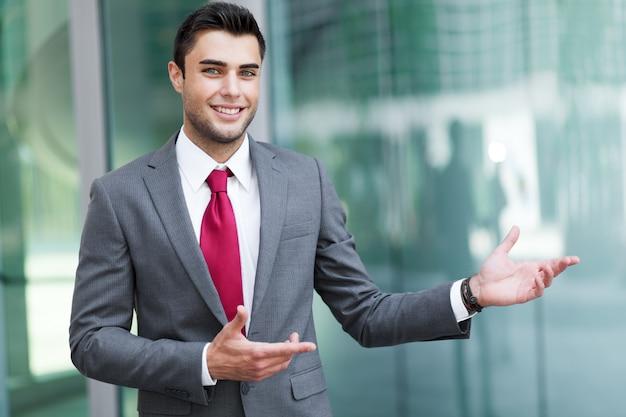 Jeune homme d'affaires en plein air vous souhaite la bienvenue