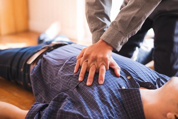 Jeune homme d'affaires pompe sur la poitrine pour les premiers soins cpr d'urgence.