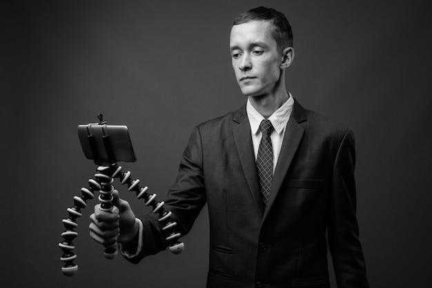 Jeune homme d'affaires portant un costume contre un mur gris en noir et blanc