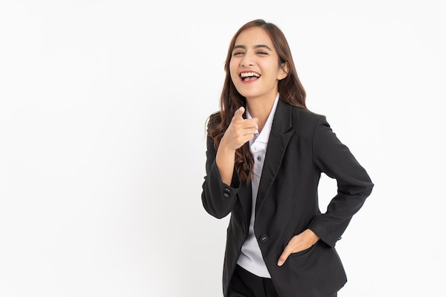 Jeune homme d'affaires portant un costume pointant vers la caméra avec une expression de rire avec de l'espace