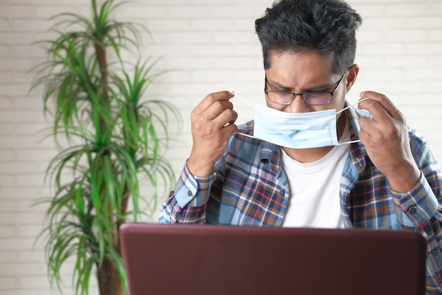 Jeune homme d'affaires portant un masque de protection et travaillant sur ordinateur portable