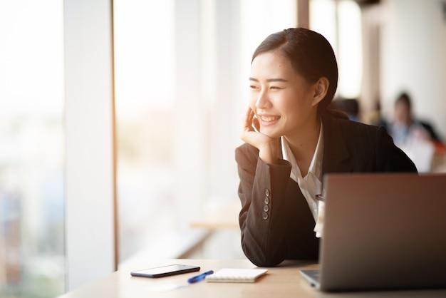 Un jeune homme d'affaires porte un costume noir au bureau.