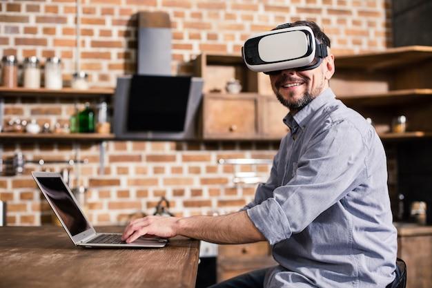 Jeune homme d'affaires positif portant un casque tout en utilisant son ordinateur portable