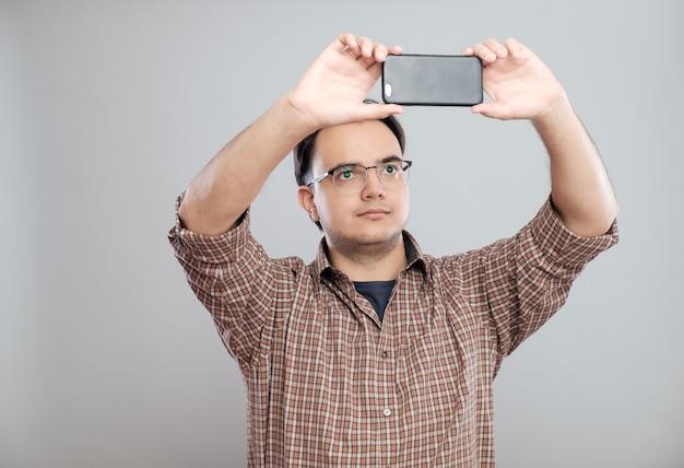 Jeune homme d'affaires prenant des photos avec un téléphone mobile