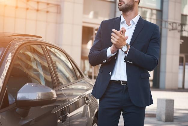 Jeune homme d'affaires près d'une nouvelle voiture en attente d'une réunion