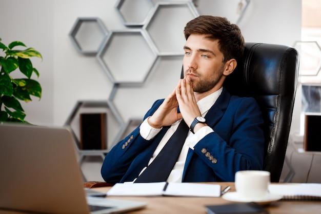 Jeune homme d'affaires prospère, assis sur le lieu de travail, fond de bureau.