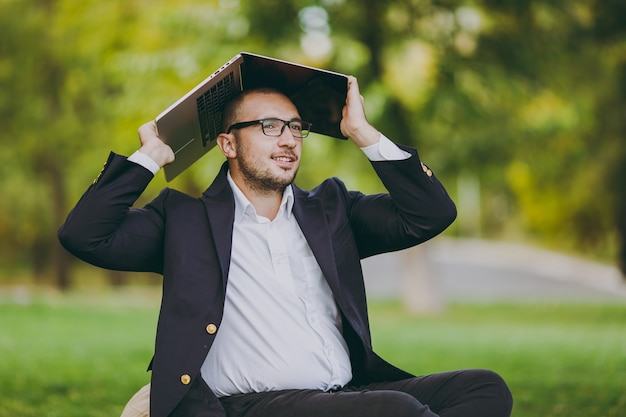 Jeune homme d'affaires prospère en chemise blanche, costume classique, lunettes. l'homme s'asseoir sur un pouf doux sous un ordinateur portable couvert dans le parc de la ville sur une pelouse verte à l'extérieur sur la nature. bureau mobile, concept d'entreprise.