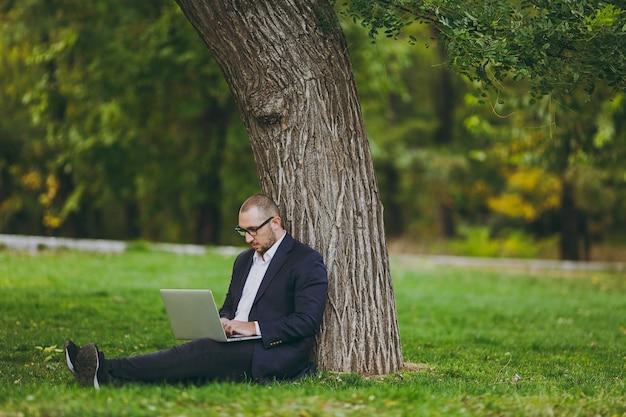 Jeune homme d'affaires prospère en chemise blanche, costume classique, lunettes. l'homme s'assoit sur le sol en herbe, travaille sur un ordinateur portable dans le parc de la ville sur une pelouse verte à l'extérieur sur la nature. bureau mobile, concept d'entreprise.