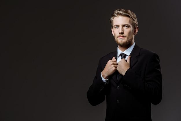 Jeune homme d'affaires prospère, correction de veste