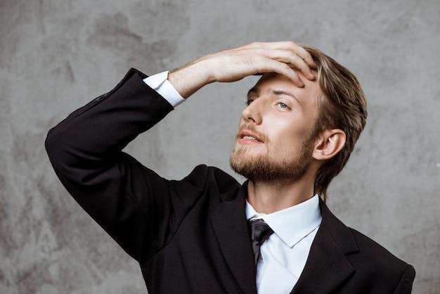 Jeune homme d'affaires prospère, corrigeant les cheveux