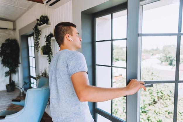 Jeune homme d'affaires prospère dans les écouteurs debout et regardant par la fenêtre dans son appartement