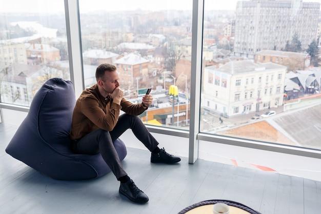 Un jeune homme d'affaires prospère est assis près d'une grande fenêtre dans le bureau et se détend