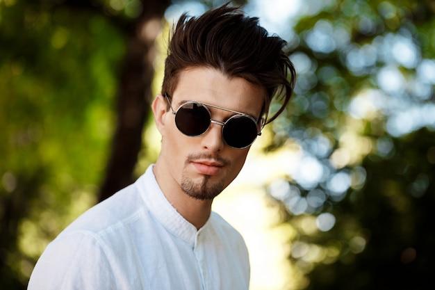 Jeune homme d'affaires prospère à lunettes de soleil souriant, se promenant dans la ville ensoleillée.