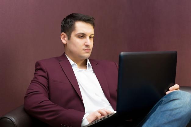 Jeune homme d'affaires prospère avec un ordinateur portable à la main.