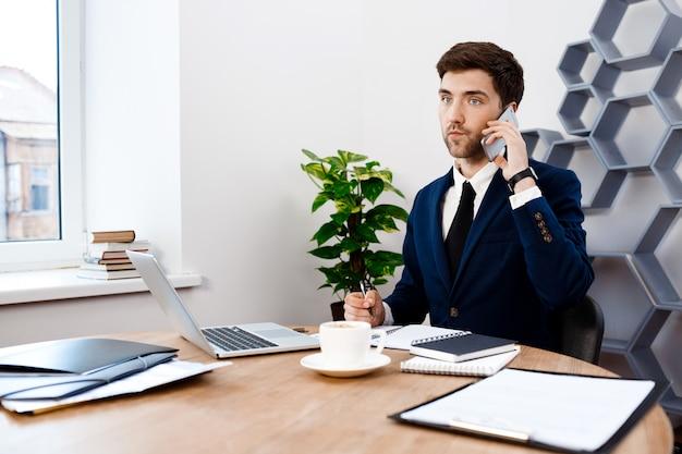 Jeune homme d'affaires prospère, parlant au téléphone, fond de bureau.