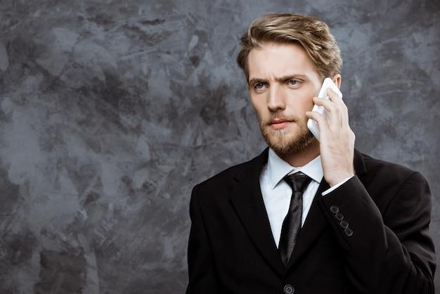 Jeune homme d'affaires prospère, parlant au téléphone