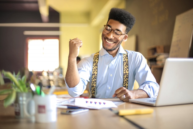 Jeune homme d'affaires prospère travaillant depuis son bureau