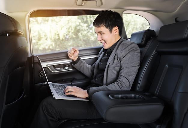 Jeune homme d'affaires prospère utilisant un ordinateur portable alors qu'il était assis sur le siège arrière de la voiture