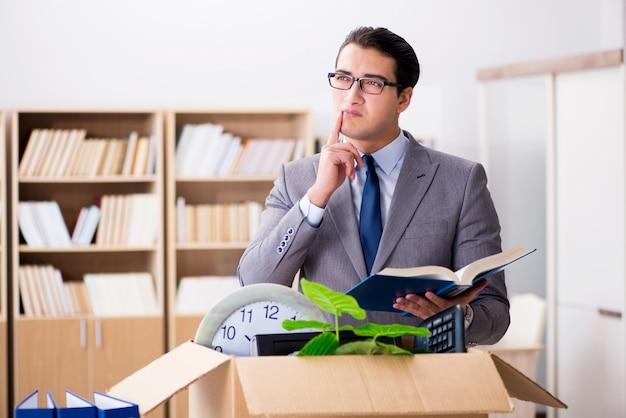 Jeune homme d'affaires qui déménage des bureaux après avoir été licencié