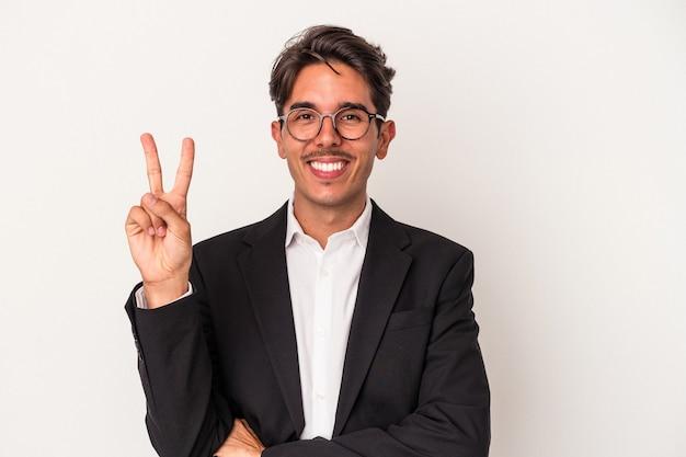 Jeune homme d'affaires de race mixte isolé sur fond blanc montrant le numéro deux avec les doigts.