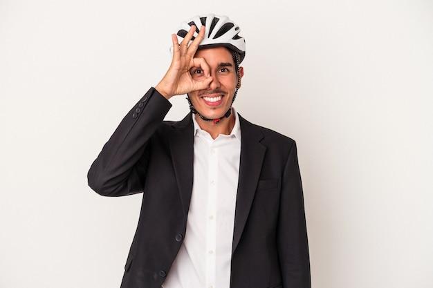 Jeune homme d'affaires de race mixte portant un casque de vélo isolé sur fond blanc excité en gardant un geste ok sur les yeux.