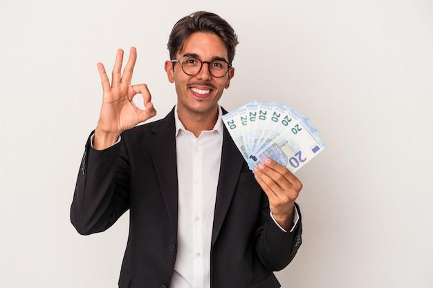 Jeune homme d'affaires de race mixte tenant des factures isolées sur fond blanc gai et confiant montrant un geste ok.