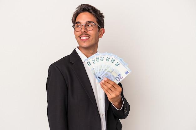 Jeune homme d'affaires de race mixte tenant des factures isolées sur fond blanc regarde de côté souriant, gai et agréable.