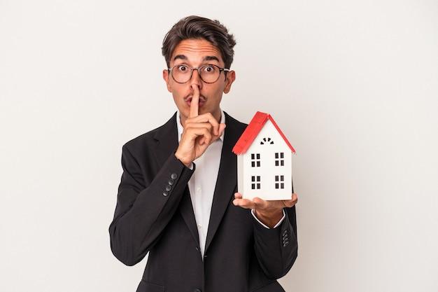 Jeune homme d'affaires de race mixte tenant une maison de jouets isolée sur fond blanc gardant un secret ou demandant le silence.