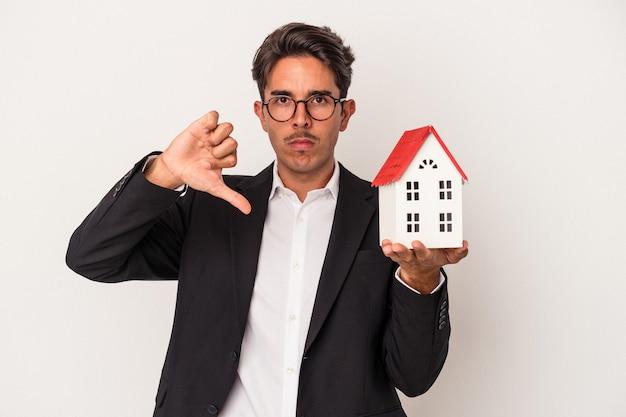 Jeune homme d'affaires de race mixte tenant une maison de jouets isolée sur fond blanc montrant un geste d'aversion, les pouces vers le bas. notion de désaccord.