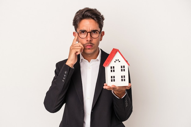 Jeune homme d'affaires de race mixte tenant une maison de jouets isolée sur fond blanc pointant le temple avec le doigt, pensant, concentré sur une tâche.
