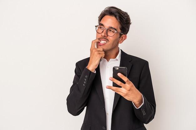 Jeune homme d'affaires de race mixte tenant un téléphone portable isolé sur fond blanc détendue en pensant à quelque chose en regardant un espace de copie.