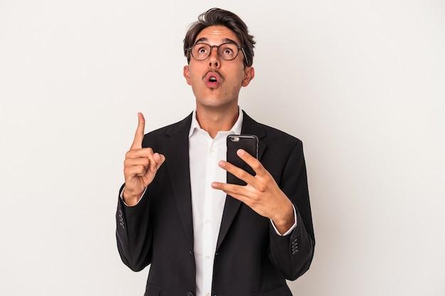 Jeune homme d'affaires de race mixte tenant un téléphone portable isolé sur fond blanc pointant vers le haut avec la bouche ouverte.