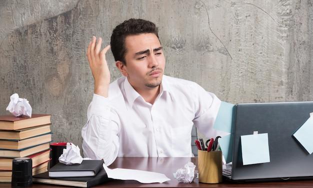 Jeune homme d'affaires à la recherche d'un ordinateur portable avec une expression perplexe au bureau.