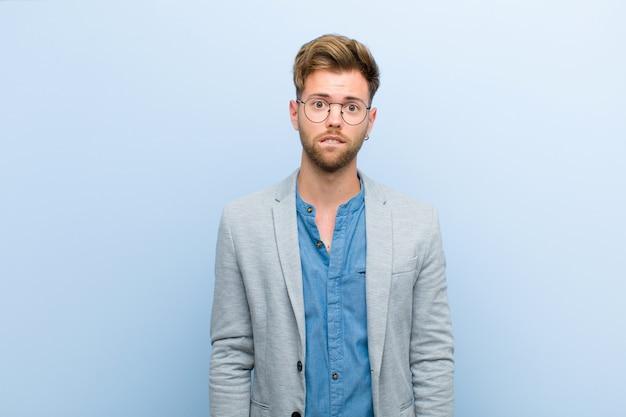 Jeune homme d'affaires à la recherche perplexe et confuse, se mordant la lèvre avec un geste nerveux, ne connaissant pas la réponse au problème sur fond bleu