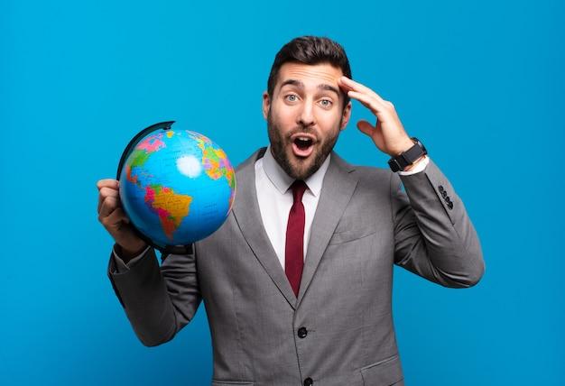 Jeune homme d'affaires à la recherche de plaisir, étonné et surpris, souriant et réalisant une bonne nouvelle incroyable et incroyable tenant une carte du globe terrestre