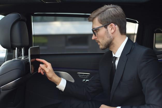 Jeune homme d'affaires réfléchi assis dans la voiture de luxe et utilisant sa tablette.