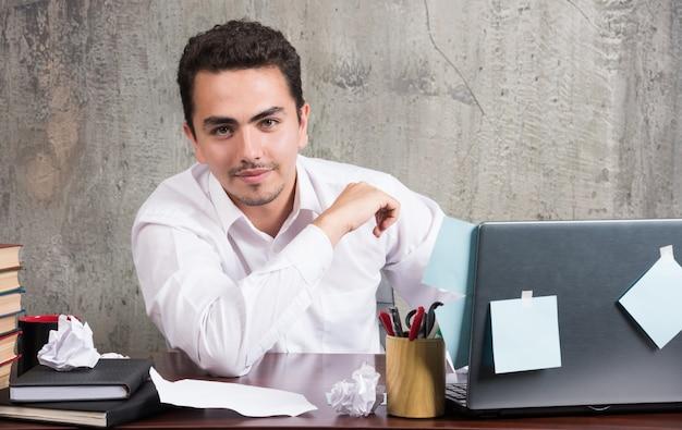 Jeune homme d'affaires regardant la caméra avec une expression heureuse au bureau.