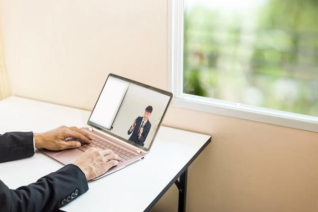 Jeune homme d'affaires regardant la leçon en ligne et étudiant à domicile.