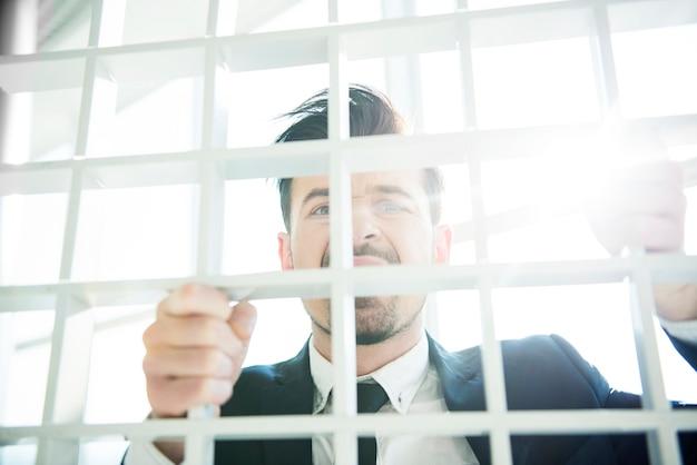 Jeune homme d'affaires regarde la caméra à travers la grille.