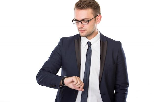 Jeune homme d'affaires regarde ses montres, isolé